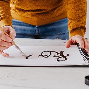 foto van het schilderen van letters in een schetsboek